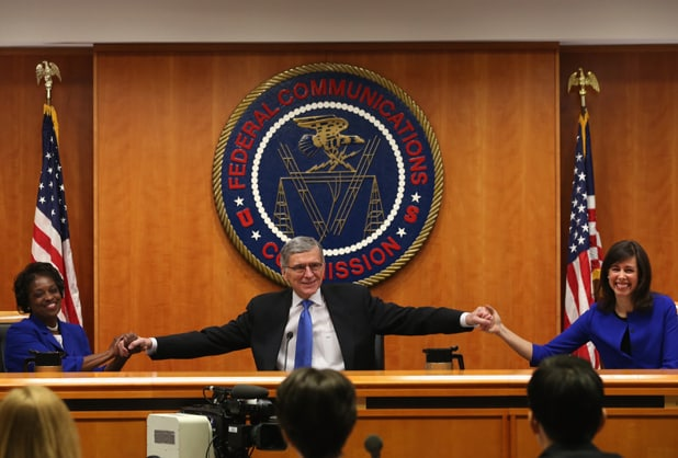 FCC net neutrality vote: Chairman Tom Wheeler (C) holds hands with FCC Commissioners Mignon Clyburn (L) and Jessica Rosenworcel (Mark Wilson/Getty Images)