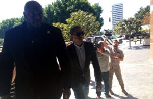 """Pharrell Williams arrives at court in Los Angeles with a bodyguard for the """"Blurred Lines"""" trial"""