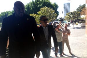 "Pharrell Williams arrives at court in Los Angeles with a bodyguard for the ""Blurred Lines"" trial"