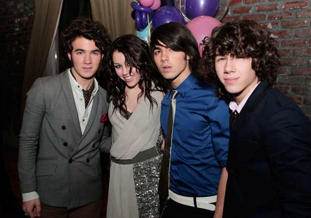 2008 - Kevin (L), Joe and Nick (R), pose with actress/singer Miley Cyrus at 'Hannah Montana and Miley Cyrus: Best of Both Worlds Concert' Premiere afterparty