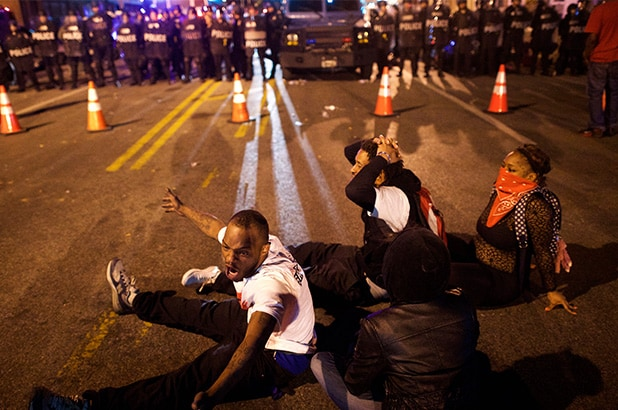 BALTIMORE, MD - APRIL 28: Protestors defy curfew in front of police officers the night after citywide riots over the death of Freddie Gray on April 28, 2015 in Baltimore, Maryland. Freddie Gray, 25, was arrested for possessing a switch blade knife April 12 outside the Gilmor Houses housing project on Baltimore's west side. According to his attorney, Gray died a week later in the hospital from a severe spinal cord injury he received while in police custody. (Photo by Mark Makela/Getty Images)