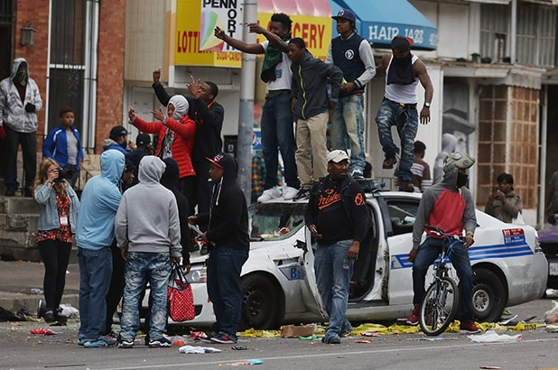 Caption:BALTIMORE, MD - APRIL 27: Demonstrators climb on a destroyed Baltimore Police car in the street near the corner of Pennsylvania and North avenues during violent protests following the funeral of Freddie Gray April 27, 2015 in Baltimore, Maryland. Gray, 25, who was arrested for possessing a switch blade knife April 12 outside the Gilmor Homes housing project on Baltimore's west side. According to his attorney, Gray died a week later in the hospital from a severe spinal cord injury he received while in police custody. (Photo by Chip Somodevilla/Getty Images)