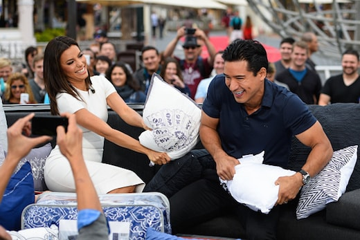 """UNIVERSAL CITY, CA - APRIL 22: Eva Longoria and Mario Lopez have a pillow fight at """"Extra"""" at Universal Studios Hollywood on April 22, 2015 in Universal City, California. (Photo by Noel Vasquez/Getty Images)"""