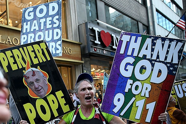 NEW YORK, NY - SEPTEMBER 24: A demonstrator holds signs on Fifth Avenue before the arrival of Pope Francis at St. Patrick's Cathedral on September 24, 2015 in New York City. Pope Francis will land at John F. Kennedy Airport after a two-day visit to Washington D.C. and will conduct a number of events while in New York including a motorcade through Central Park and Mass in Madison Square Garden. (Photo by Justin Sullivan/Getty Images)