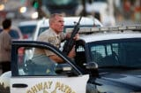 A California Highway Patrol officer stands with his weapon