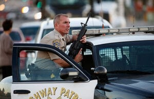 SAN BERNARDINO, CA - DECEMBER 02: A California Highway Patrol officer stands with his weapon as authorities pursued the suspects in a shooting that occurred at the Inland Regional Center on December 2, 2015 in San Bernardino, California. Police continue to search for suspects in the shooting that left at least 14 people dead and another 17 injured. (Photo by Sean M. Haffey/Getty Images)