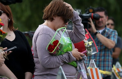 A woman holds flowers outside the site of the San Bernardino mass shooting