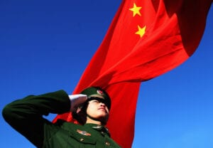 A Chinese flag waves behind a saluting soldier china