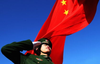 A Chinese flag waves behind a saluting soldier