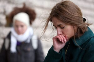 A woman bows her head at a rally to honor journalists killed at Charlie Hebdo