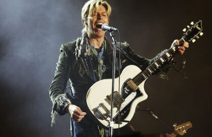 David Bowie performs with a guitar in 2004