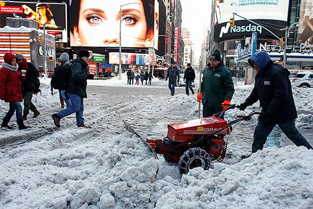Times Square employees clean a snow covered street in Times Square on January 24, 2016 in New York.