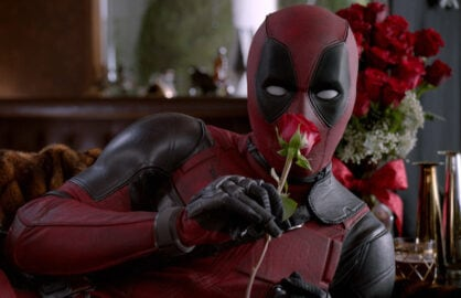 """A still from an ad for """"Deadpool,"""" showing the title character holding a rose"""