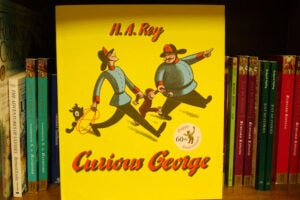 "A ""Curious George"" book on a shelf"