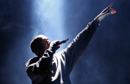 Kanye West performs under a spotlight