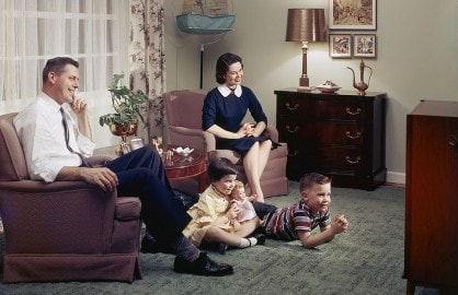 A young family watching television together in their lounge, 1957. (Photo by Harold M. Lambert/Getty Images)