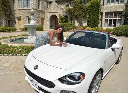 """LOS ANGELES, CA - MAY 11: 2016 Playmate of the Year Eugena Washington signs a copy of her Playboy issue on her new All-New 2017 Fiat 124 Spider at Playboy's 2016 Playmate of the Year Announcement at the Playboy Mansion on May 11, 2016 in Los Angeles, California. (Photo by Charley Gallay/Getty Images for Playboy)"""