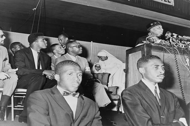 Muhammad Ali attends a speech by Elijah Muhammad