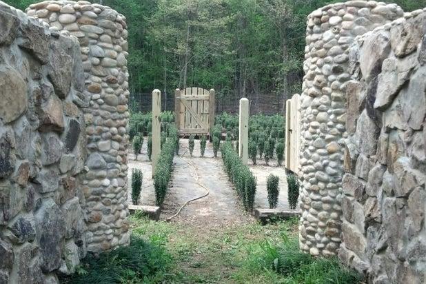 A entrada do labirinto de John com muros de pedra, pequenas roseiras e uma porta de madeira