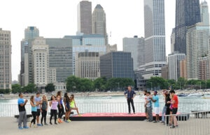 Phil Keoghan and the previously eliminated contestants await the winners of Season 29 in Chicago. (Michele Crowe/CBS)