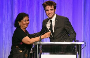 BEVERLY HILLS, CA - AUGUST 02: HFPA President Meher Tatna and Robert Pattinson speak onstage at the Hollywood Foreign Press Association's Grants Banquet at the Beverly Wilshire Four Seasons Hotel on August 2, 2017 in Beverly Hills, California. (Photo by Kevin Winter/Getty Images)